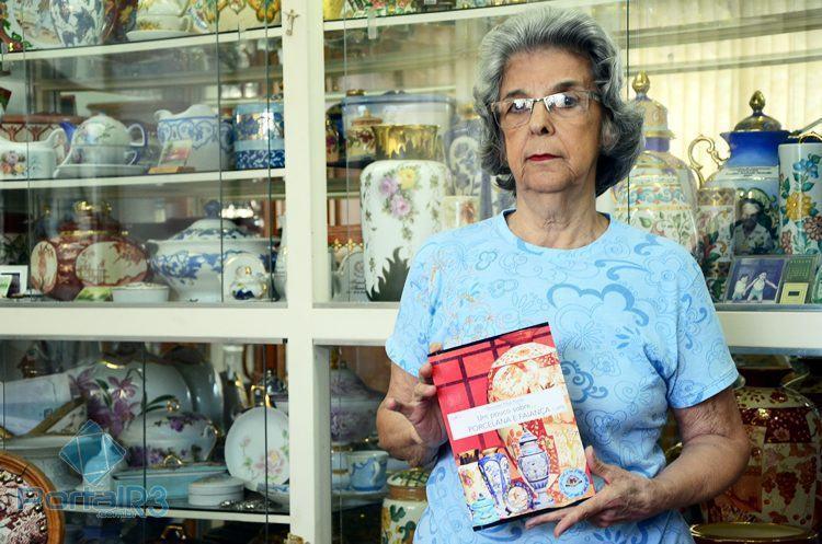 Professora Therezinha exibe seu primeiro livro sobre pintura em porcelana e faiança. (Foto: Luis Claudio Antunes/PortalR3)
