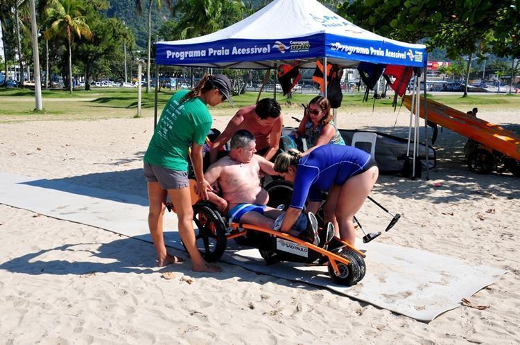 Monitores com formação em Educação Física auxiliam as pessoas com deficiência ou limitações e idosos a entrarem no mar com as cadeiras anfíbias, coletes salva-vidas e bóias. (Foto: : Luis Gava/PMC)