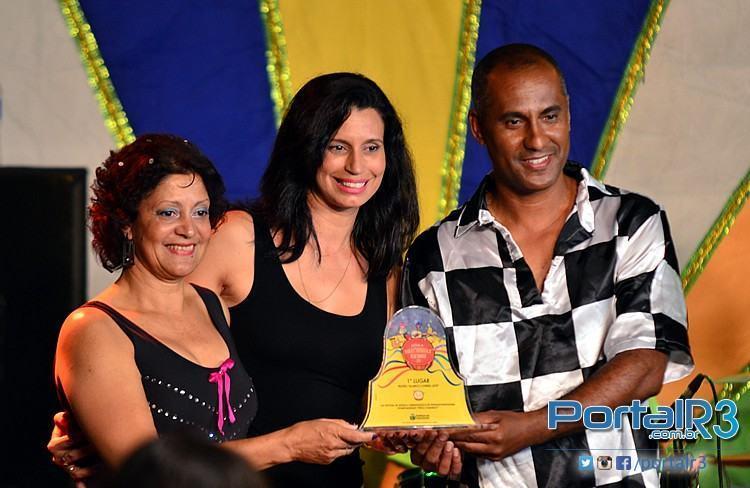 Guilherme e Valquíria recebem o troféu de campeão da secretária de Educação, Cidinha Pedroso. (Foto: Luis Claudio Antunes/PortalR3)