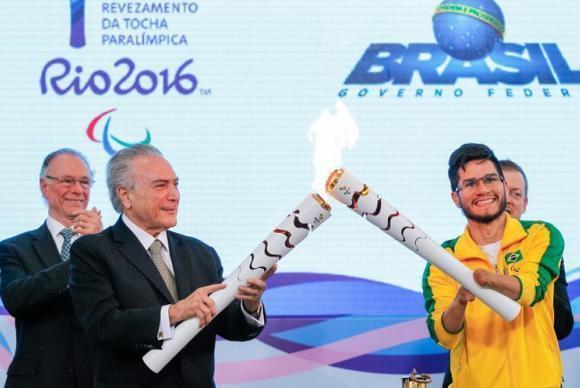 O presidente interino Michel Temer e o velocista Yohansson Nascimento acendem a tocha paralímpica no Palácio do Planalto. (Foto: Beto Barata/Presidência da República)